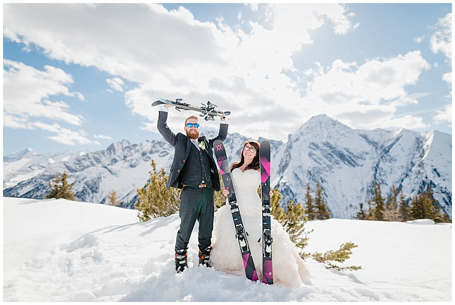 Bec and Dan posing with their skis in the snow on the wedding day in Austria