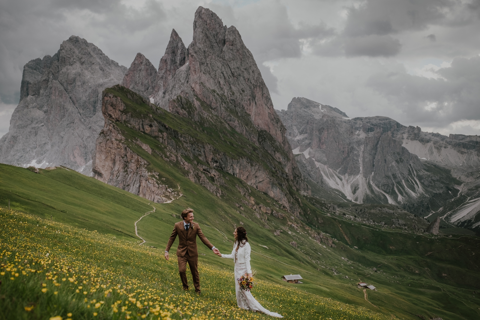 Groom leading bride up the steep mountain hillside of Seceda in the Dolomites with rocky knife-edge peaks in the distance